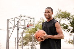 Image of african cheerful basketball player standing in the street with basketball hoop at background. Looking at camera.