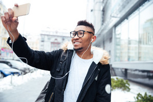 Image of african cheerful man holding his cellphone in hands and make a selfie while listen to music outdoors.