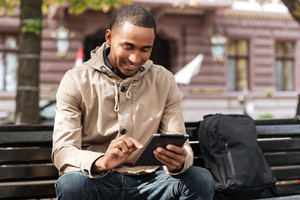 Image of african cheerful man with tablet sitting on wooden bench near backpack and chatting. Look at tablet.