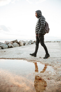 Image of african concentrated man dressed in warm clothes walking on the beach. Looking aside.