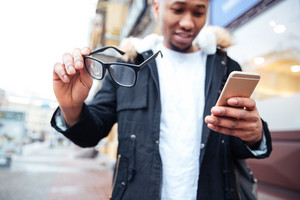 Image of african happy man holding his eyeglasses and phone in hands while walking outdoors. Look at phone.
