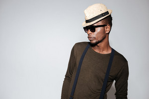 Image of african young man wearing hat and glasses standing in studio. Isolated over grey background.