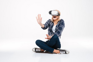 Image of amazed woman sitting on floor wearing VR glasses isolated on a white background.