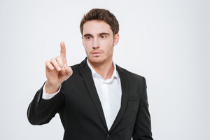 Image of attractive businessman standing at studio and pointing. Isolated over white background.
