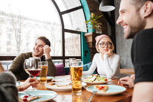 Image of attractive happy friends sitting in cafe eating and drinking alcohol.
