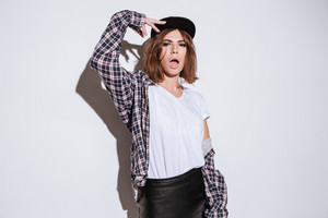 Image of attractive lady dressed in shirt in a cage print standing isolated over white background