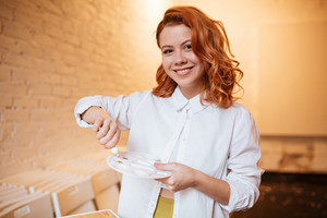 Image of attractive redhead young woman painter with oil paints and palette. Look at camera.