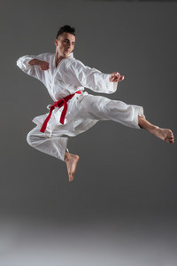 Image of attractive sportsman dressed in kimono practice in karate isolated over grey background. Looking aside.