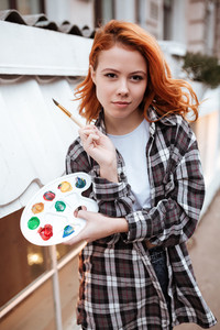 Image of attractive young lady painter with red hair walking on the street. Look at camera while holding paintbrush and palette outdoors.