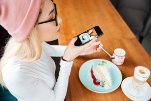 Image of attractive young lady wearing hat and glasses make photo of cake and coffee by phone while sitting in cafe.