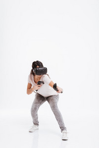 Image of attractive young woman wearing virtual reality device over white background.