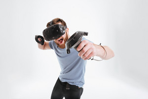 Image of bearded happy man wearing virtual reality device standing over white background with joysticks