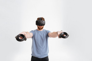 Image of bearded man wearing virtual reality device standing over white background while holding joysticks in hands.