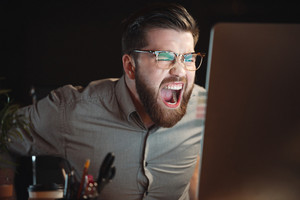 Image of bearded web designer dressed in shirt and wearing eyeglasses working late at night and looking at computer while screaming.