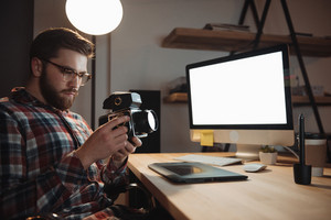 Image of bearded web designer dressed in shirt in a cage print and wearing glasses holding camera. Focus on camera.