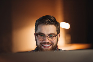 Image of bearded young happy web designer dressed in shirt in a cage print and wearing glasses working late at night and looking at computer.