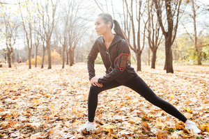 Image of beautiful runner in warm clothes and headphones looking aside in autumn park while make sport exercise