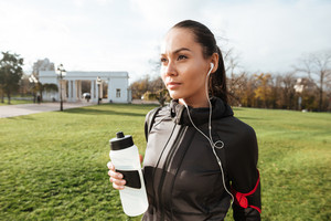 Image of beautiful runner in warm clothes looking aside in autumn park while holding bottle of water