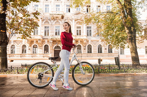 Image of beautiful woman walking with her bicycle in the city. Looking back.
