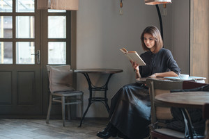 Image of beautiful young woman sitting at the table in cafe and reading book.