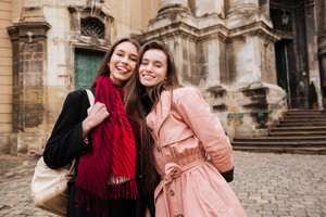 Image of beauty girls in coats. on the street. looking at the camera