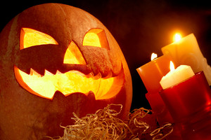 Image of big pumpkin with burning candle inside and three candles near by
