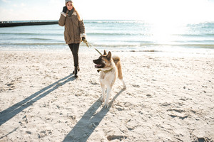 Image of blond caucasian lady walks in winter beach with dog on a leash.
