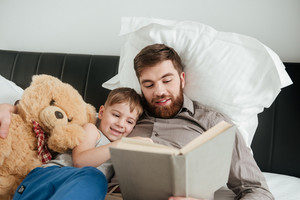 Image of boy lies at home in bed near toy with his bearded father reading fairytale book.