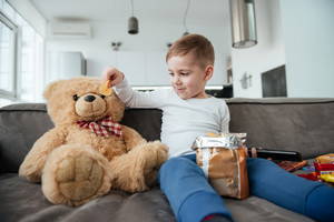 Image of boy sitting on sofa with teddy bear at home and watching TV while eating chips. Holding remote control.