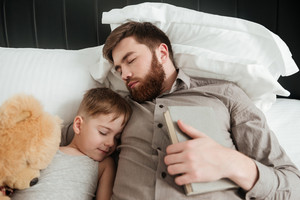 Image of boy sleeping at home in bed near toy with his bearded father holding book.