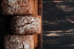 Image of bread with flour on dark wooden table background at bakery