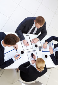 Image of business people working with papers at meeting