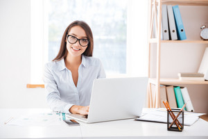 Image of businesswoman dressed in white shirt and wearing glasses sitting in her office and using laptop. Looking at camera.