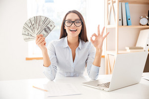 Image of businesswoman dressed in white shirt sitting in her office and holding money in hand while making Okay gesture