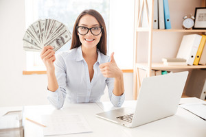 Image of businesswoman dressed in white shirt sitting in her office and holding money in hand while making thumbs up gesture