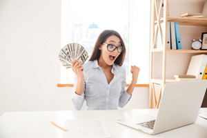 Image of businesswoman dressed in white shirt sitting in her office and holding money in hand while making winner gesture
