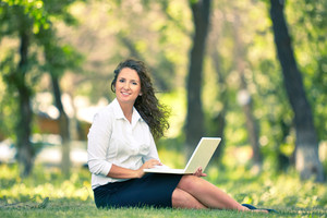 Image of businesswoman sitting on the grass and typing on the laptop