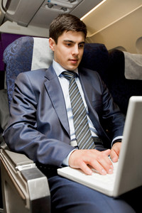 Image of busy male typing on laptop during flight