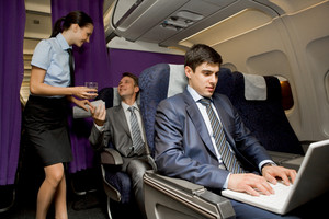 Image of busy male typing on laptop with pretty stewardess giving glass of water to successful businessman on background