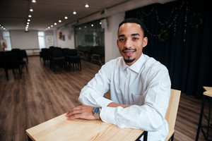 Image of cheerful african businessman sitting at the table and looking at camera. Coworking.