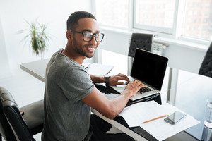 Image of cheerful african man dressed in gey t-shirt and wearing eyeglasses using laptop and sitting at the table. Looking at the camera.