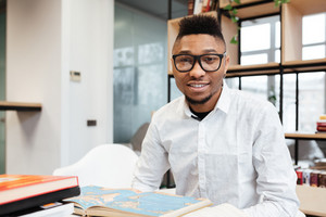 Image of cheerful african student wearing eyeglasses in library learning education material with books. Looking at camera.