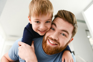 Image of cheerful bearded father dressed in blue t-shirt playing with his little cute son indoors