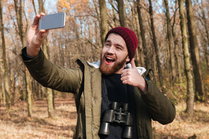 Image of cheerful bearded man wearing hat making selfie by the phone in the forest. Looking at phone and smile while making thumbs up gesture.