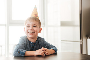 Image of cheerful birthday boy sitting in kitchen while smiling. Look aside.