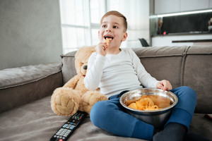 Image of cheerful boy on sofa with teddy bear at home watching TV while eating chips. Holding remote control.