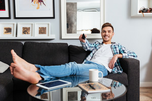 Image of cheerful bristle man dressed in shirt in a cage print lies on sofa in home and holding remote control while watching TV.