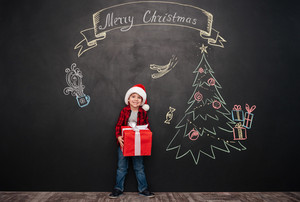 Image of cheerful child wearing hat standing near Christmas drawing on blackboard and holding a gift in hands. Looking at camera.