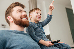 Image of cheerful father watching TV with his little cute son holding remote control.