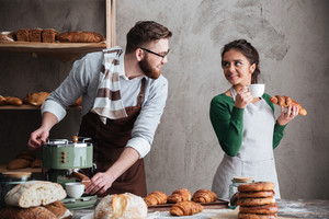 Image of cheerful loving couple bakers standing near bread and croissants drinking coffee. Looking aside.
